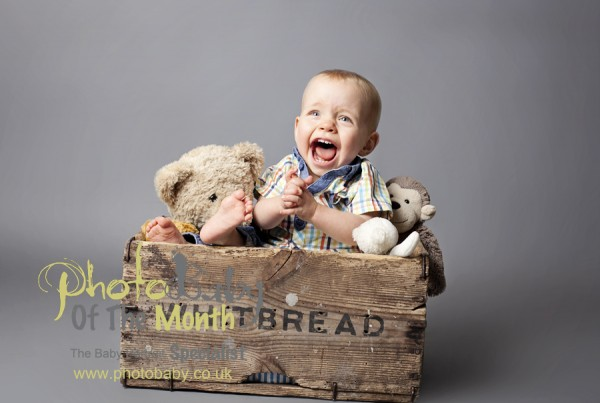 baby photography lancashire, baby in a box having a great time with his teddies.