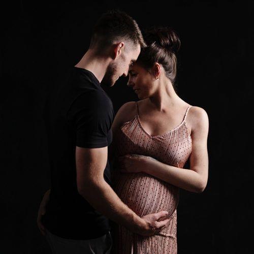 Low Key studio maternity portrait of couple, intimate, dark shadows.