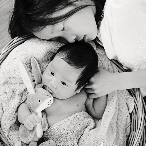 Asian sister cuddling baby brother in a basket. Black and white photo.