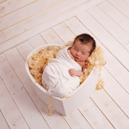 newborn baby photographed wrapped in white, lying in white heart, on white floorboards. Lancaster PhotoBaby studio portrait.